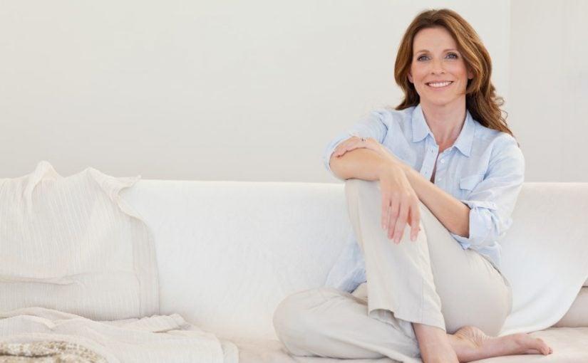 Moden kvinde der sidder på en sofa
